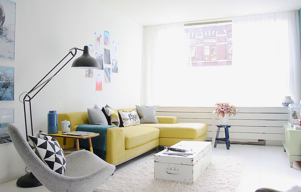 Eclectic living room in white with a bright yellow couch