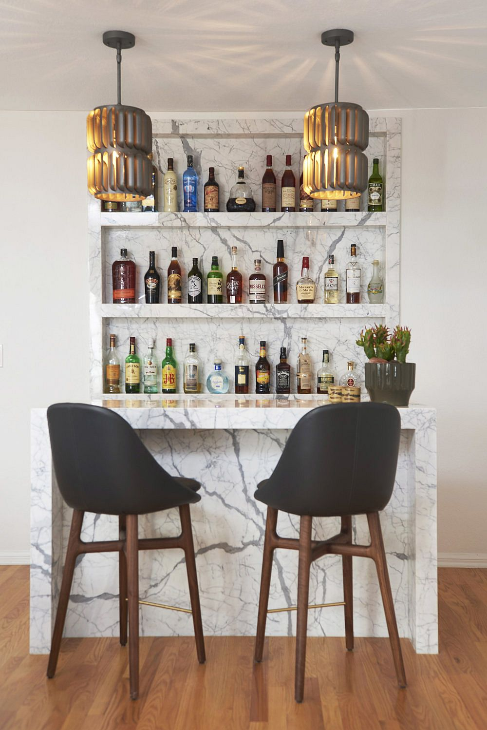 Home bar with marble backsplash and counter along with a couple of bar stools