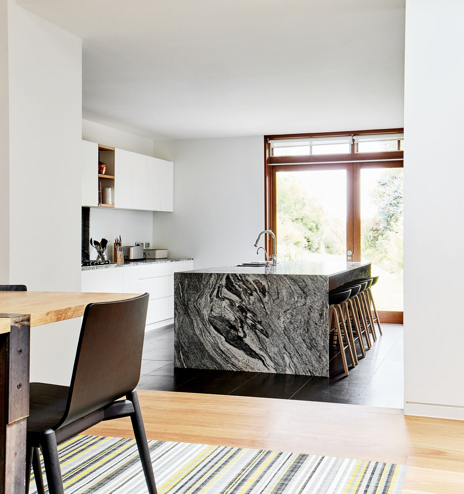 Landscape-outside-brings-ample-natural-light-into-the-kitchen-with-stunning-stone-island
