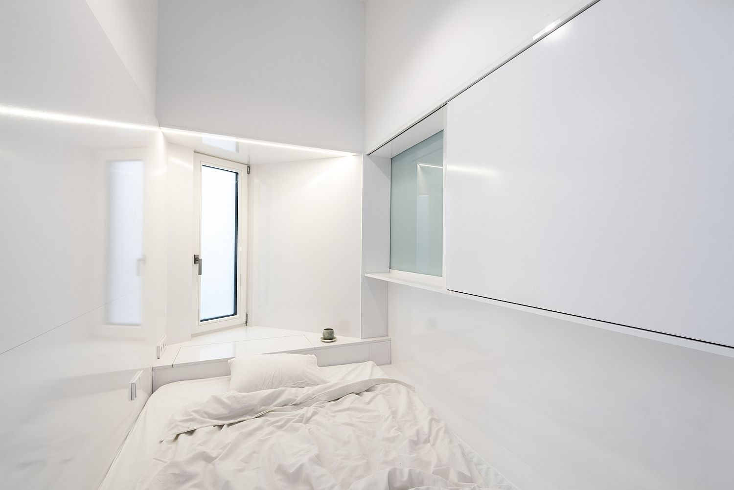 Nook above the headboard and window give the monochromatic bedroom a bright aura