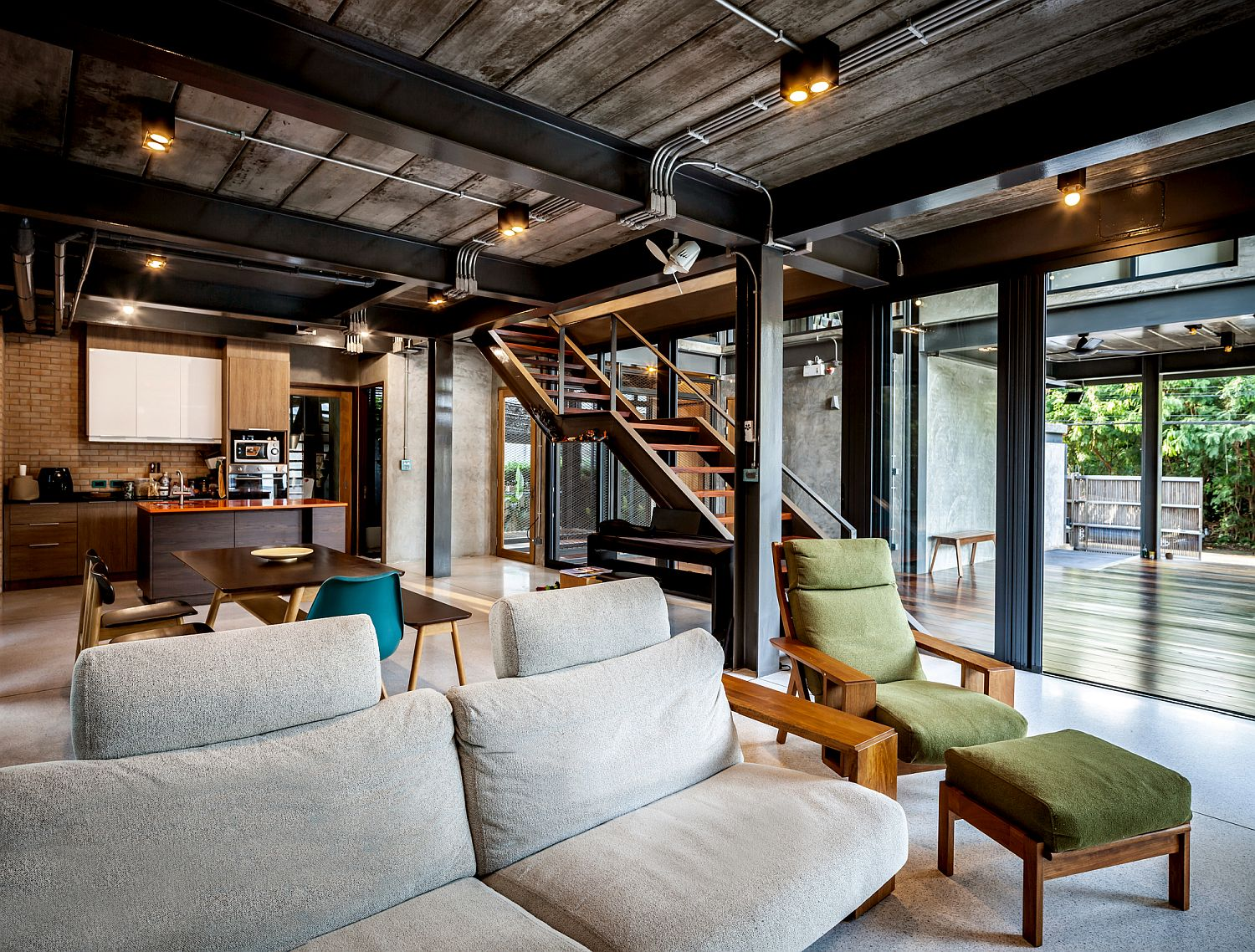 Open plan living area of the Bangkok home where nature outside takes center-stage