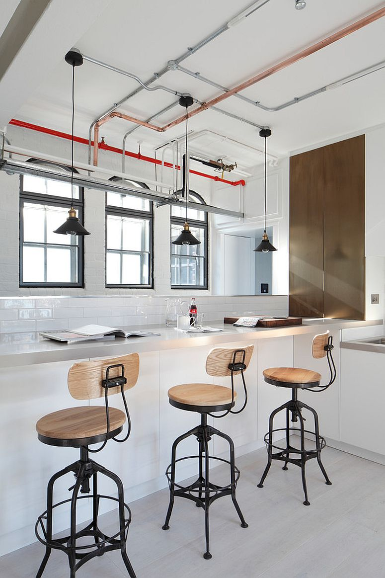 Polished-industrial-kitchen-with-bar-stools-that-match-its-style