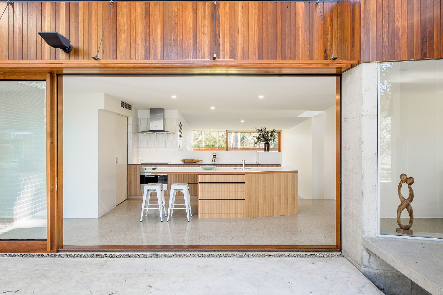 Sliding glass walls with wooden frame separate the kitchen from the garden outside