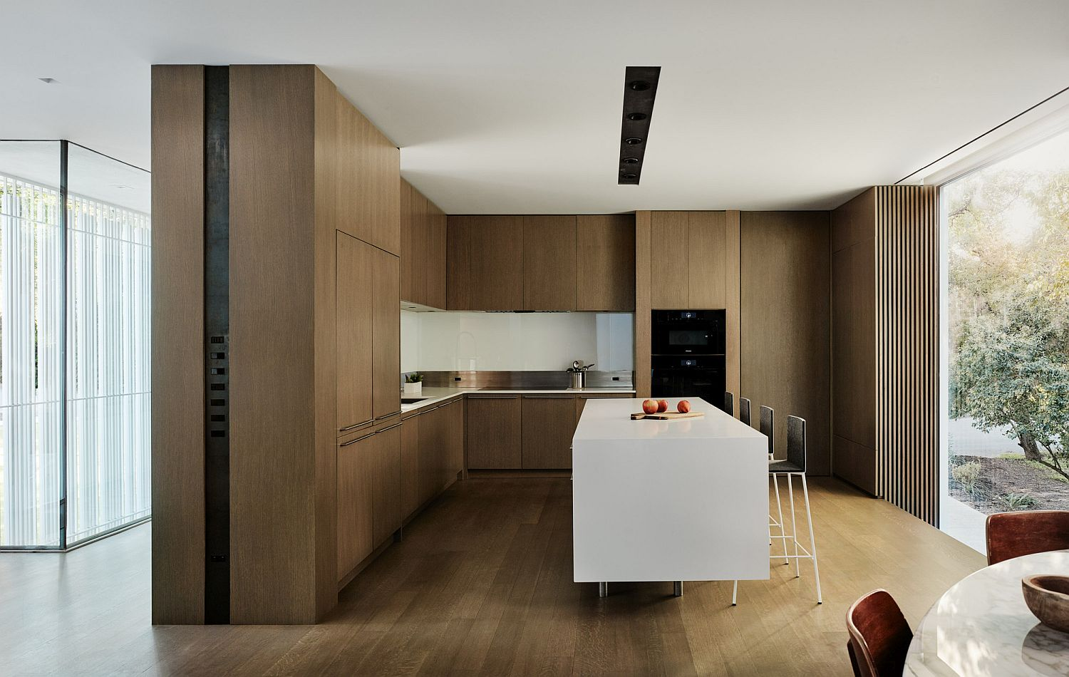 Spacious kitchen with wooden cabinets, white island and connectivity with the outdoors