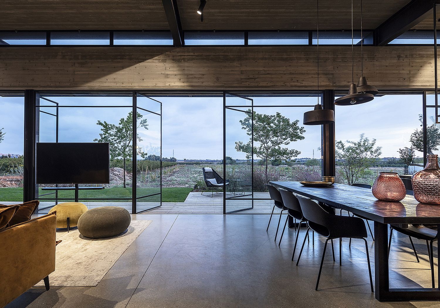 Swiveling glass doors connect the living room with the open field outside
