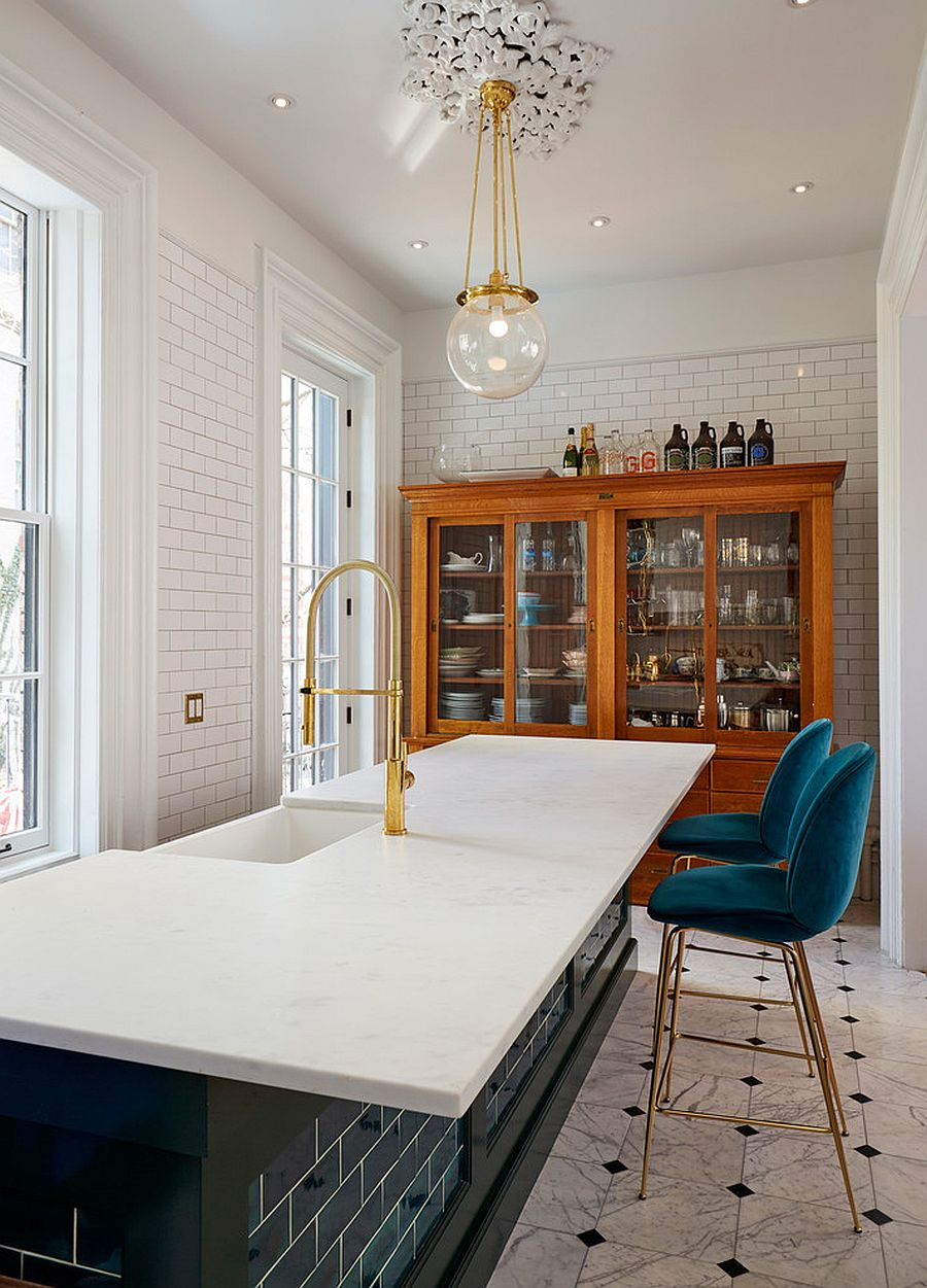 Transitional-kitchen-in-white-with-blue-and-gold-bar-stools-along-with-pendants-and-fixtures-in-gold