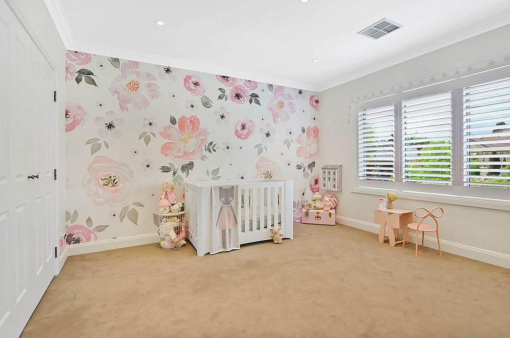 Wallpaper clad accent wall steals the show in this nursery