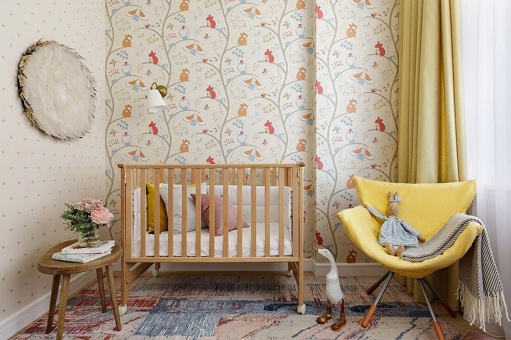 Whimsical patterns of the wallpaper add a fun flair to the nursery