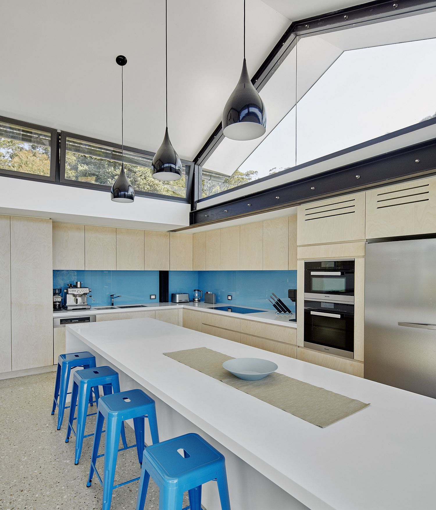 Bar stools and backsplash in blue for the spacious modern kitchen
