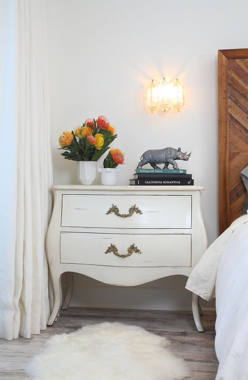 Cozy lighting and organic finishes along with midcentury decor add to the appeal of the bedroom