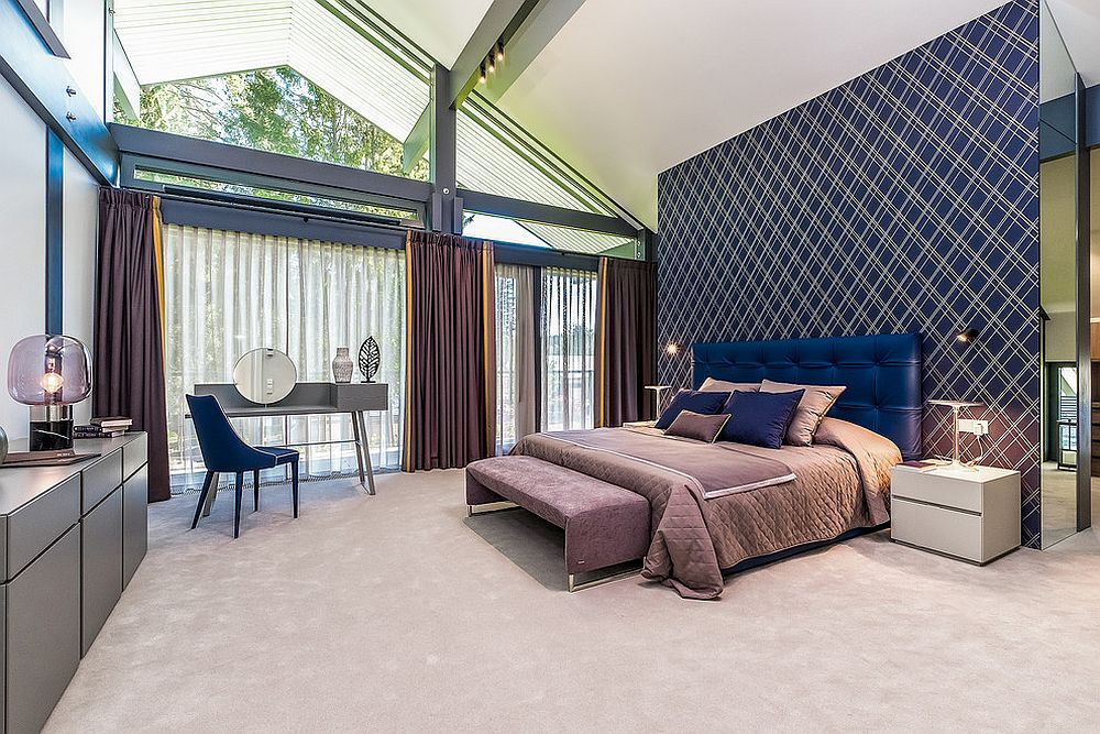 Gorgeous modern bedroom with purple headboard wall, drapes and brilliant pops of blue all around