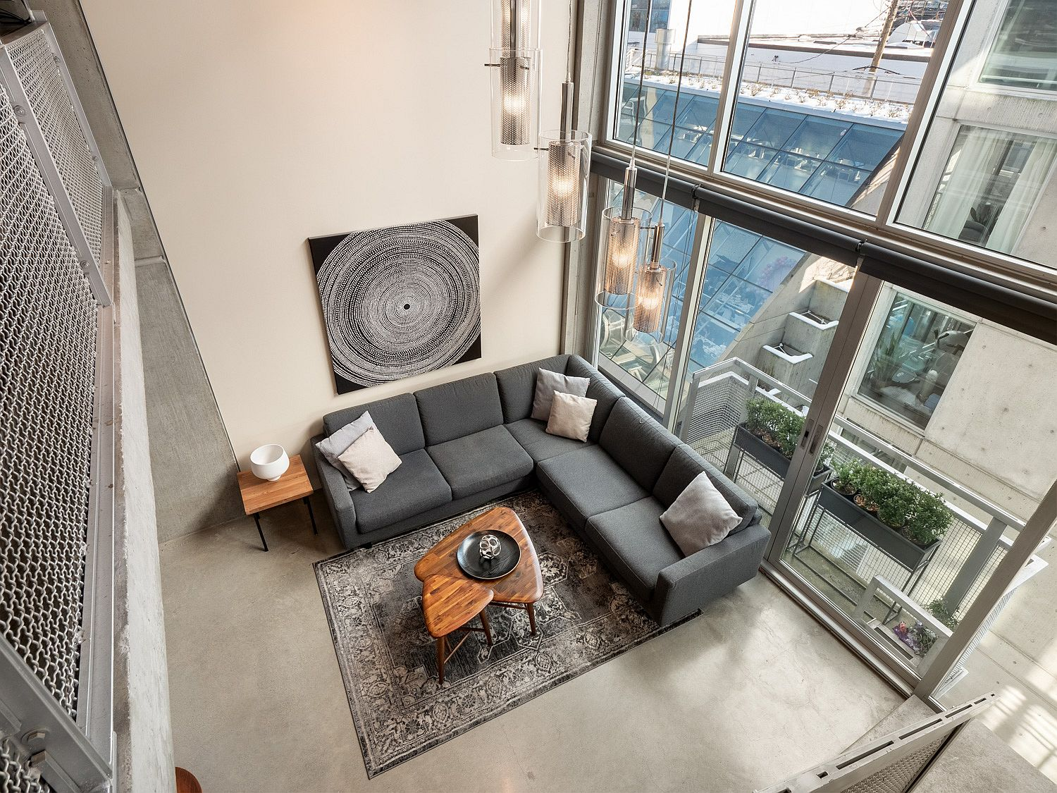 Gray sectional inside the living room fits in perfectly with its concrete-centric theme