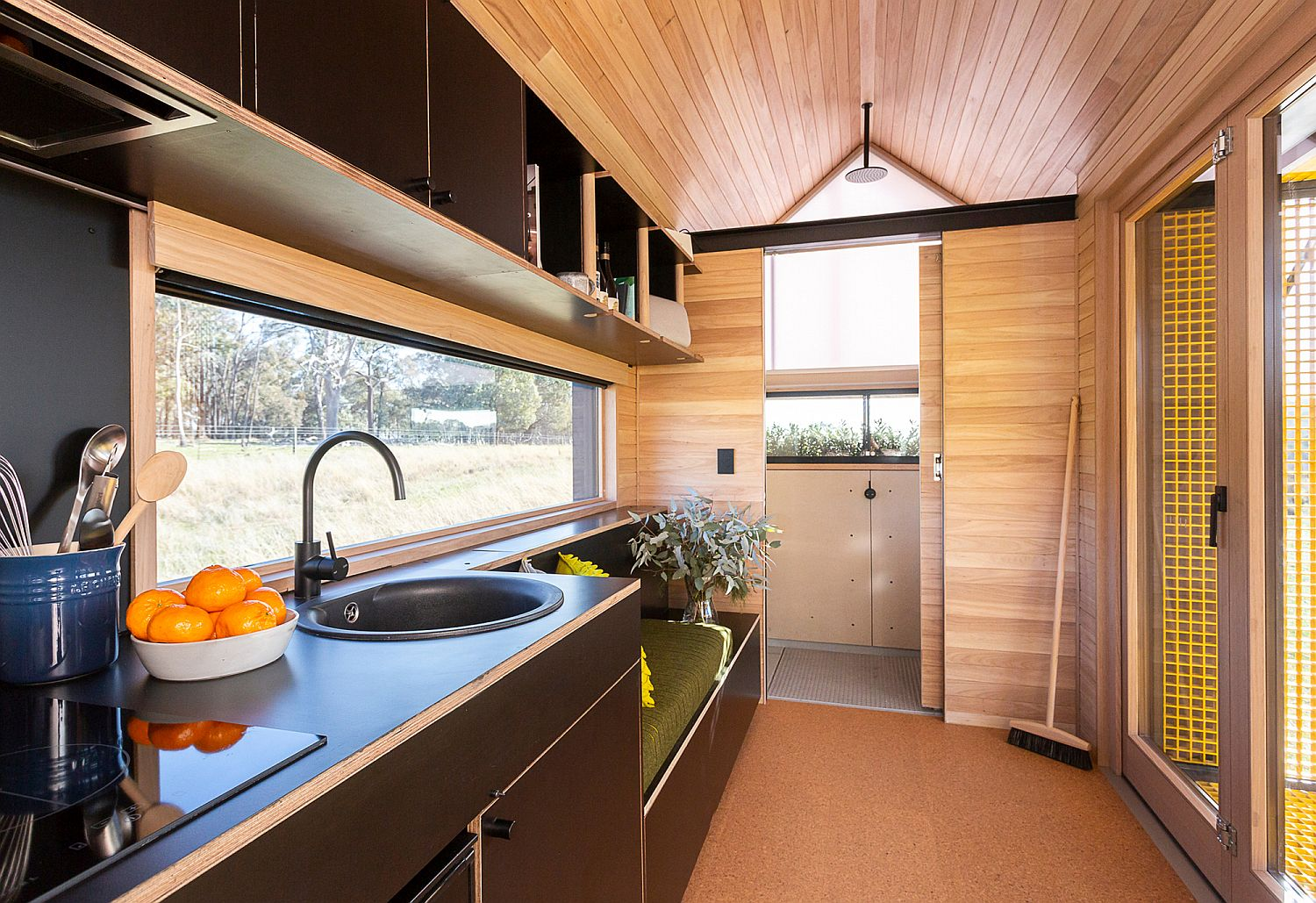 Kitchen with a sitting area next to it inside the tiny cabin home