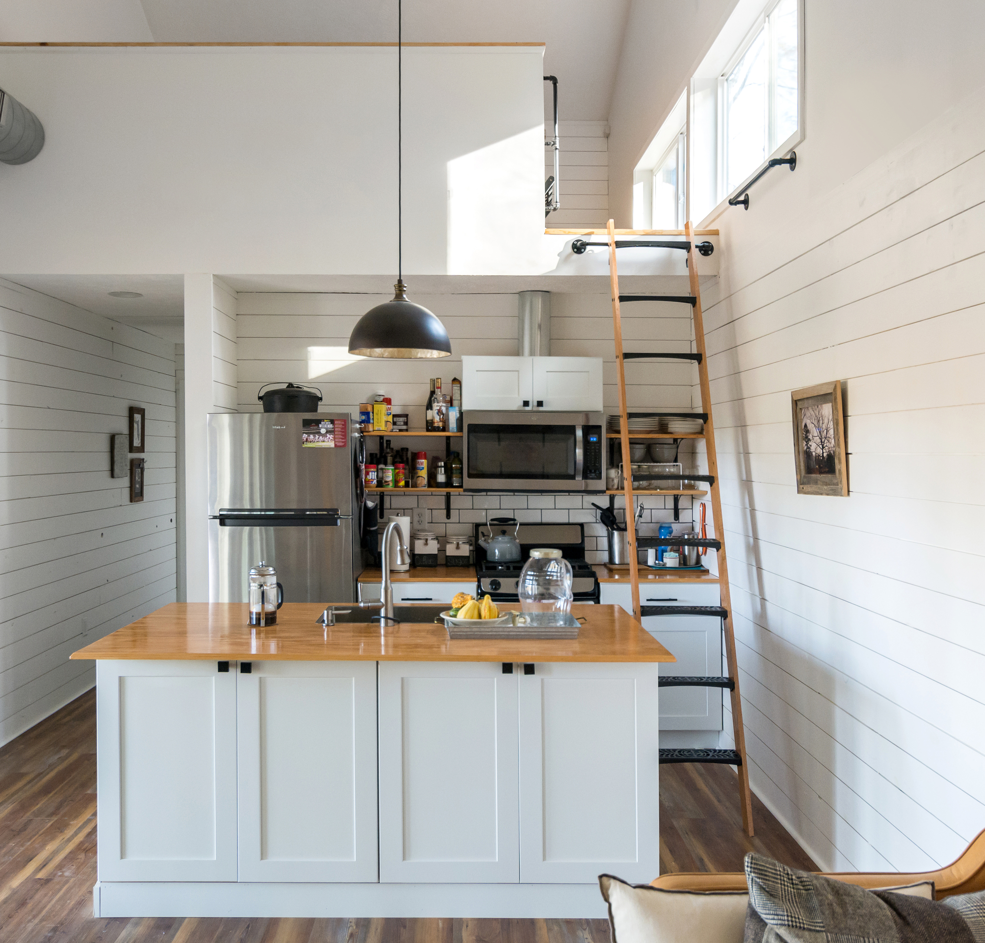 Kitchen with sleeping area above inside the tiny house