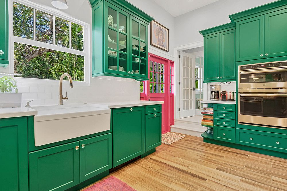 Lovely use of green cabinets in the white contemporary kitchen with ample natural light