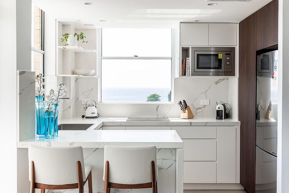 Marble brings class to the white kitchen that is well-lit