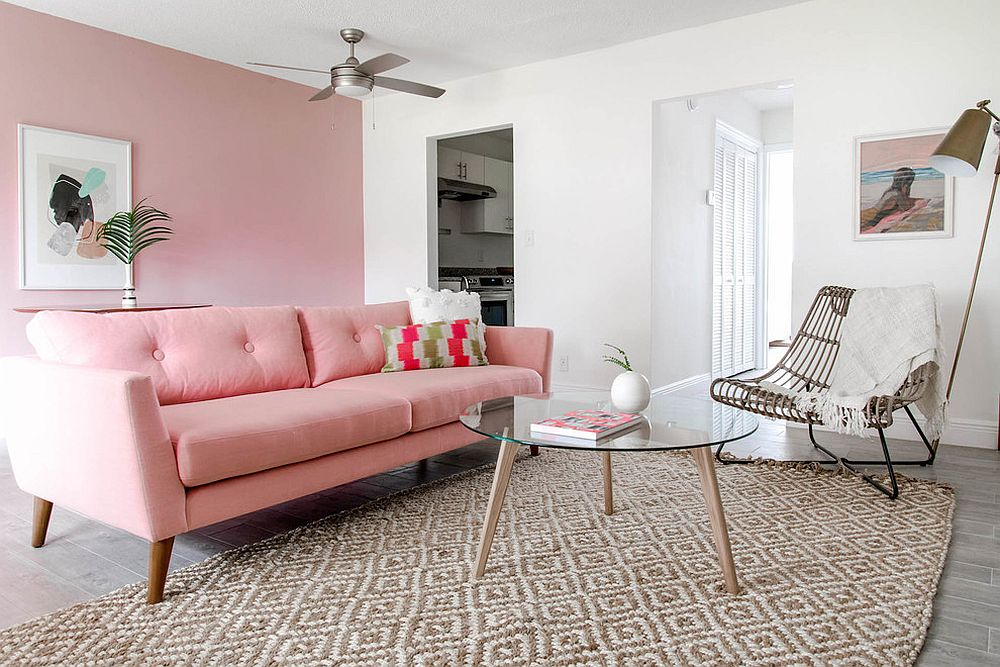 Midcentury living room with pink accent wall and a matching couch