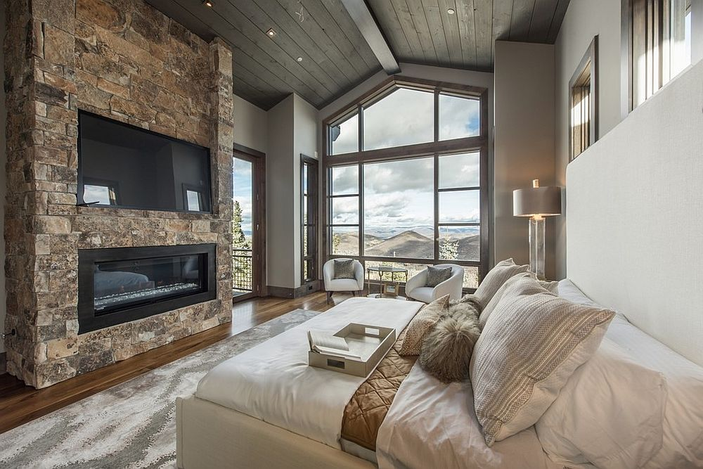 Stone-wall-with-TV-and-fireplace-for-the-modern-rustic-bedroom-that-offers-ample-luxury