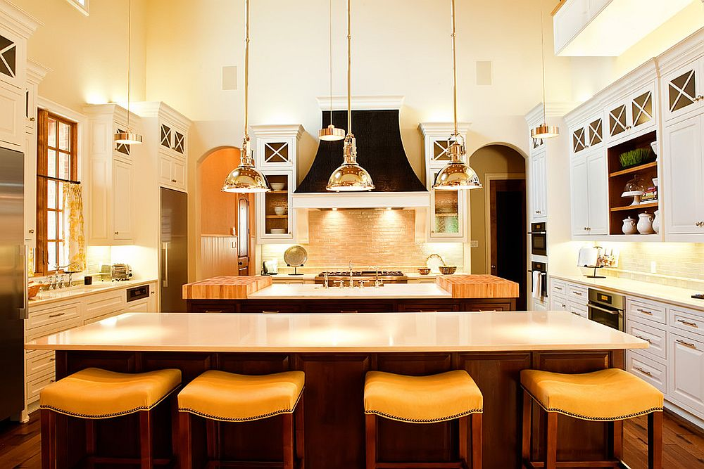 Traditional kitchen with ample lighting, metallic pendants and minimal bar stools in beige