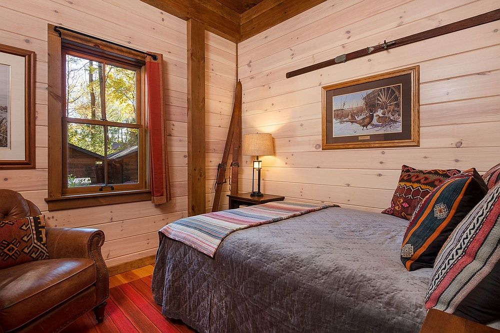Walls in wood bring warm glow to the small modern cabin bedroom