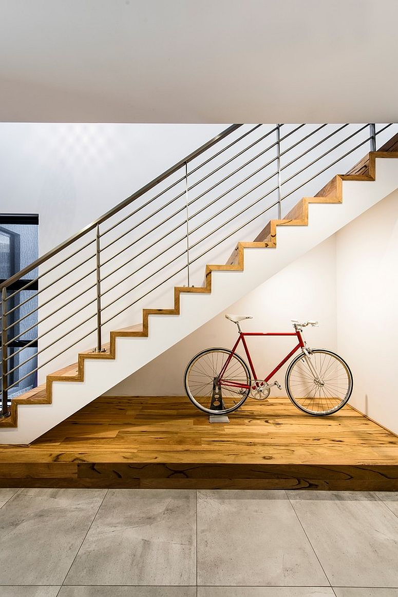Beautifully lit space underneath the stairway for the bicycle