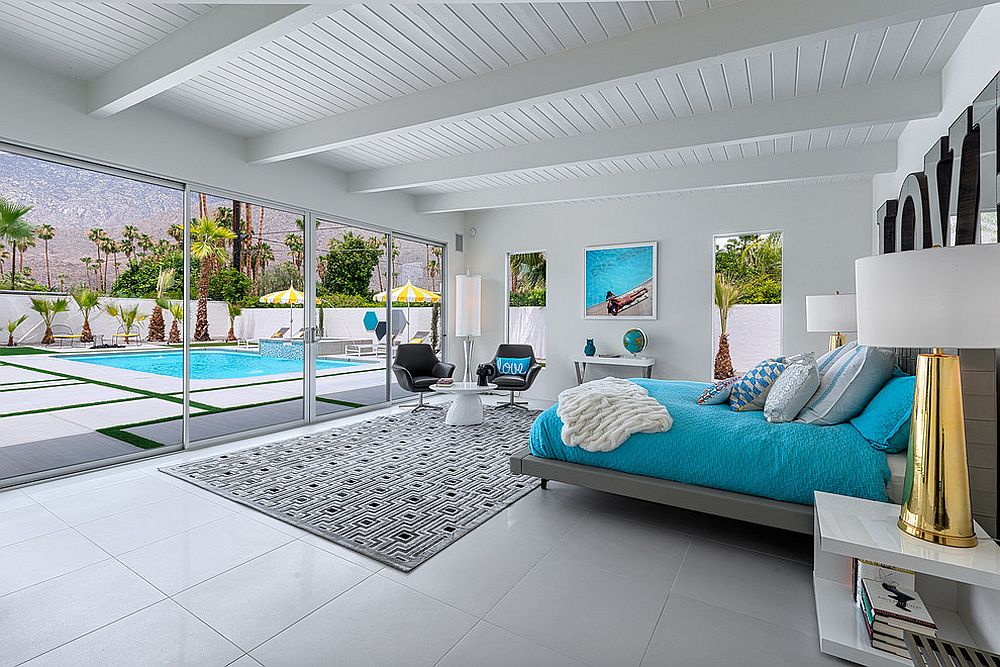 Bedding adds blue to the refined beach style bedroom connected with the pool area outside