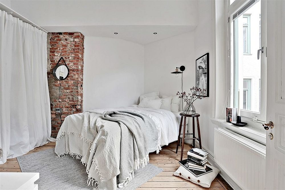 Brick wall section brings texture to the minimal bedroom in white