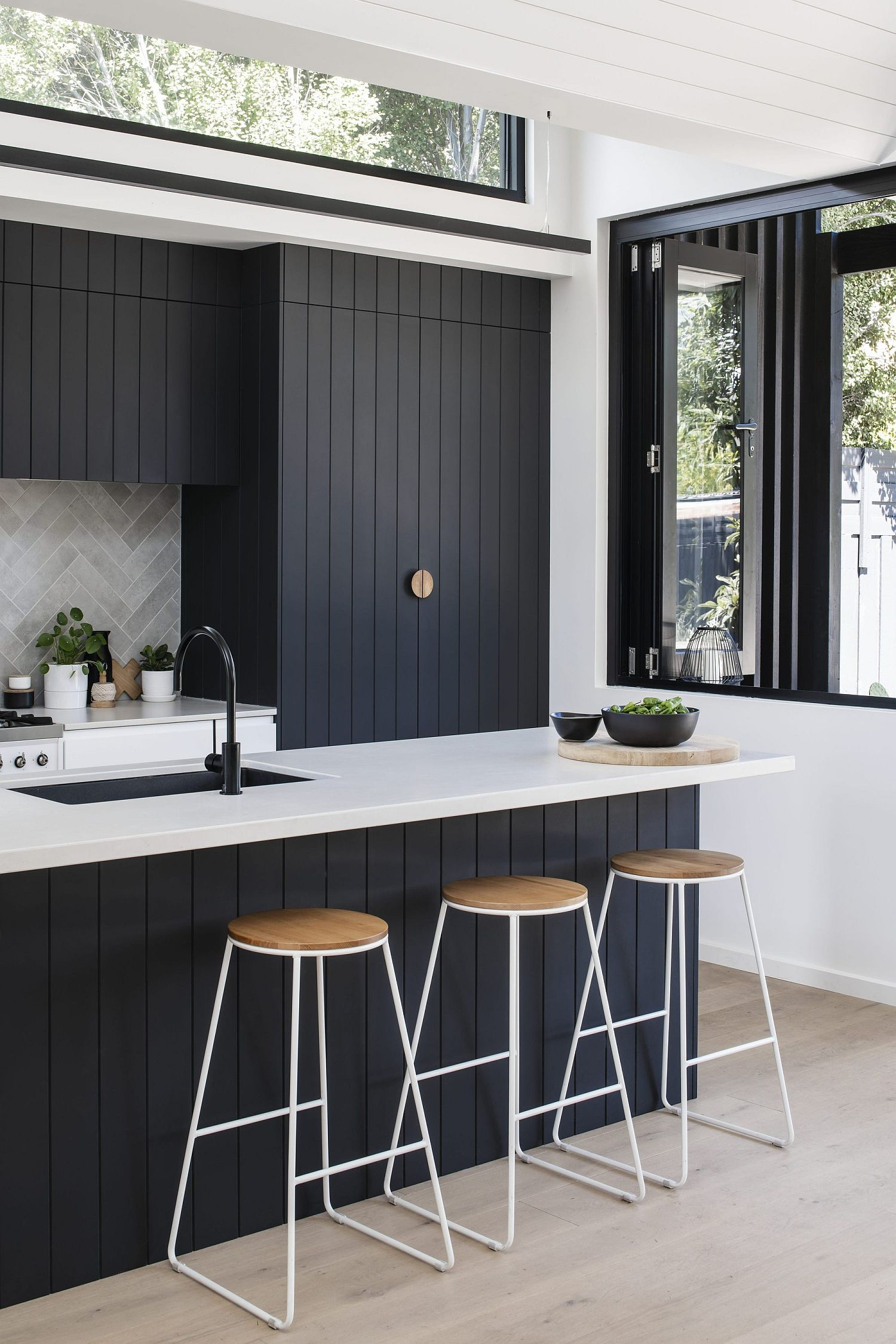 Charred and oiled cypress can be found in the modern white kitchen of the house as well