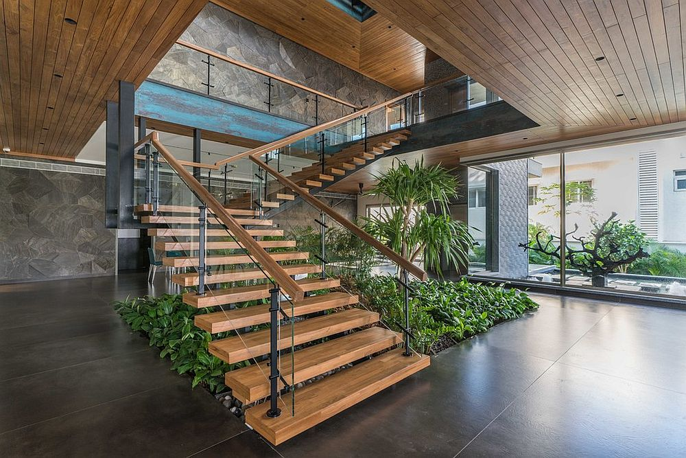 Contemporary stairway with greenery beneath it that adds ample freshness to the interior