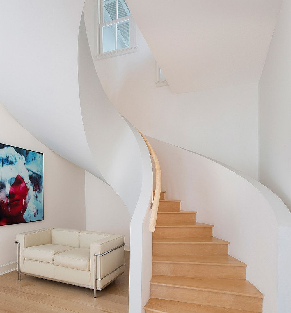 Couch under the spiral staircase offers a lovely sitting space