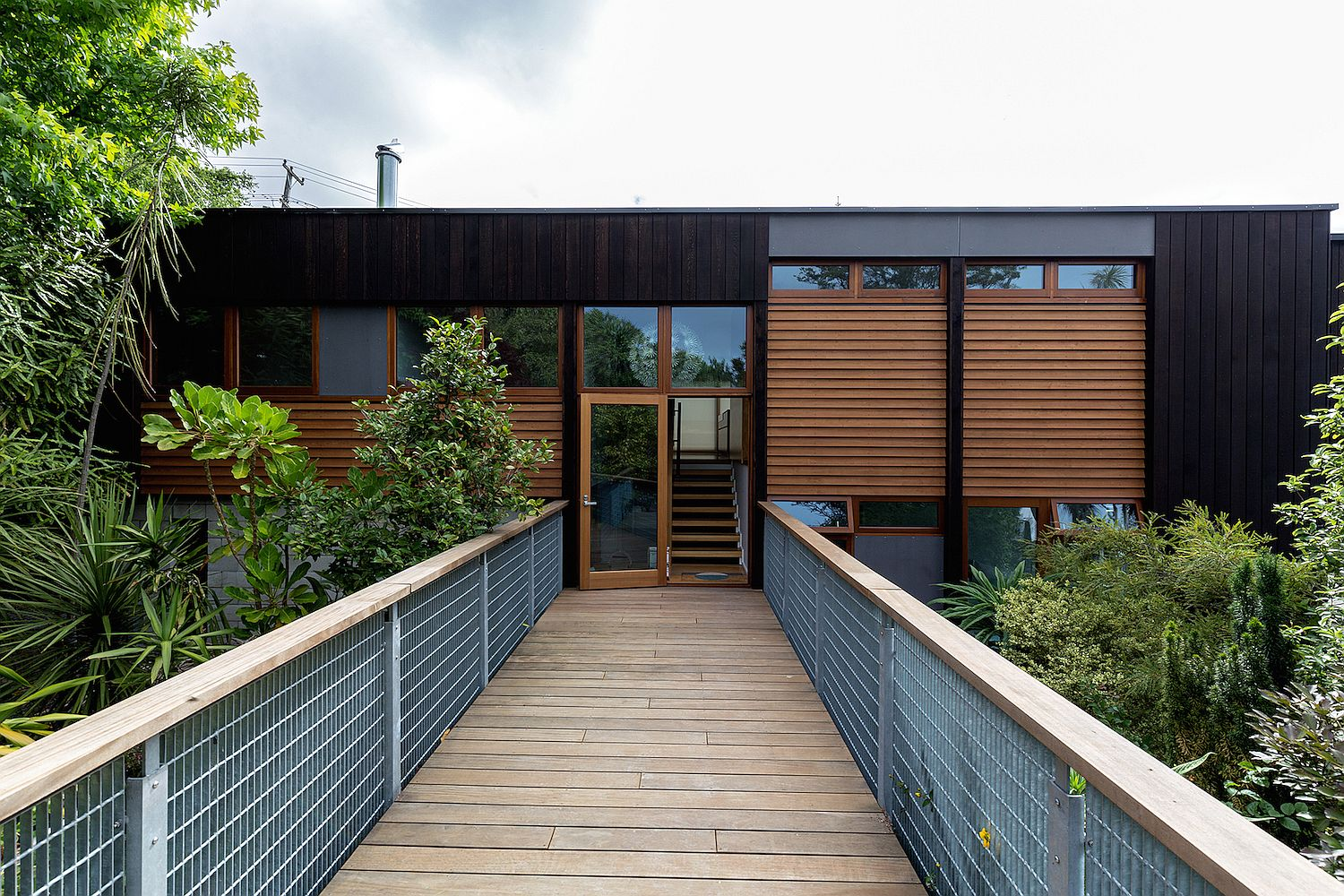Entrance to the revamped 1950s Cowey House with a wooden bridge and smart insulation