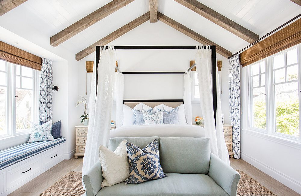 Four poster bed along with the slanting ceiling beams bring holiday vibe to this bedroom