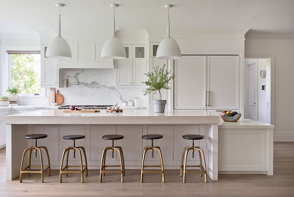 It is bar stools that add visual contrast to the all-white kitchen