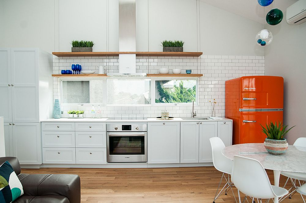 Just the addition of retro fridge in orange makes a big impact in this white kitchen