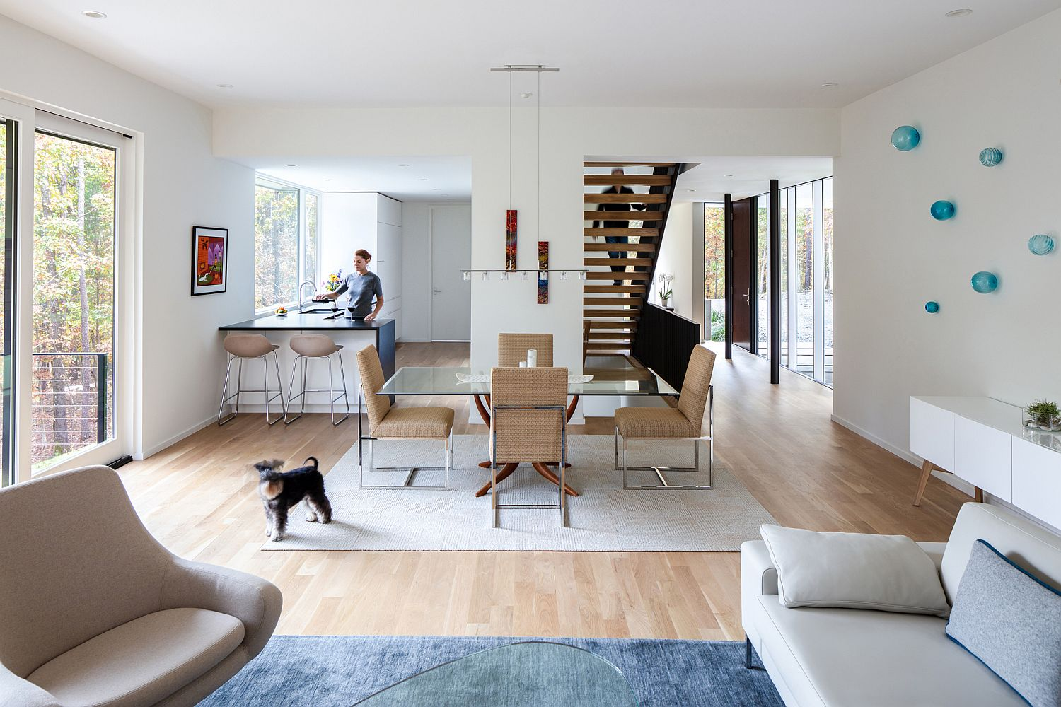 Kitchen, dining area and living space in white and wood with pops of blue