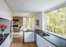 Kitchen-in-the-corner-makes-most-of-available-space-while-offering-lovelys-views-of-the-woods-217x155