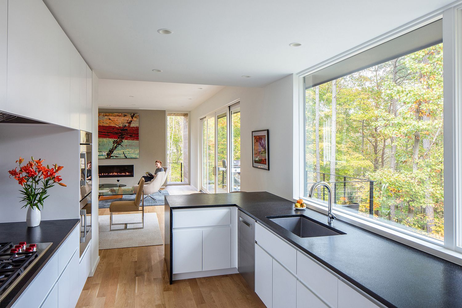 Kitchen in the corner makes most of available space while offering lovelys views of the woods