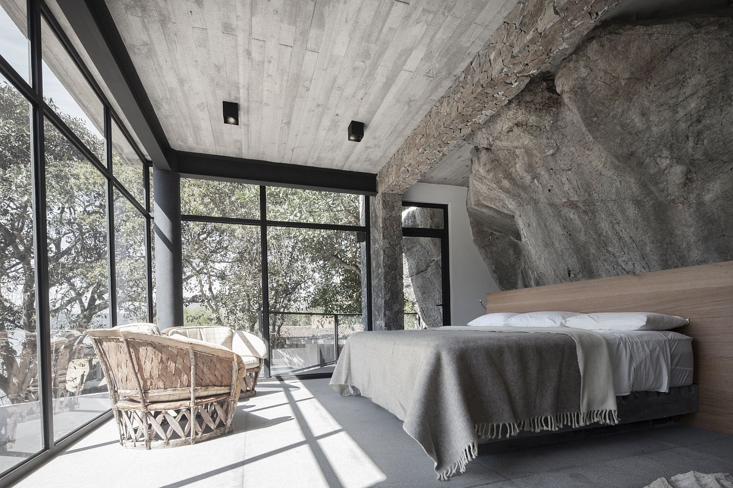 Large natural rock becomes the headboard wall for this contemporary bedroom