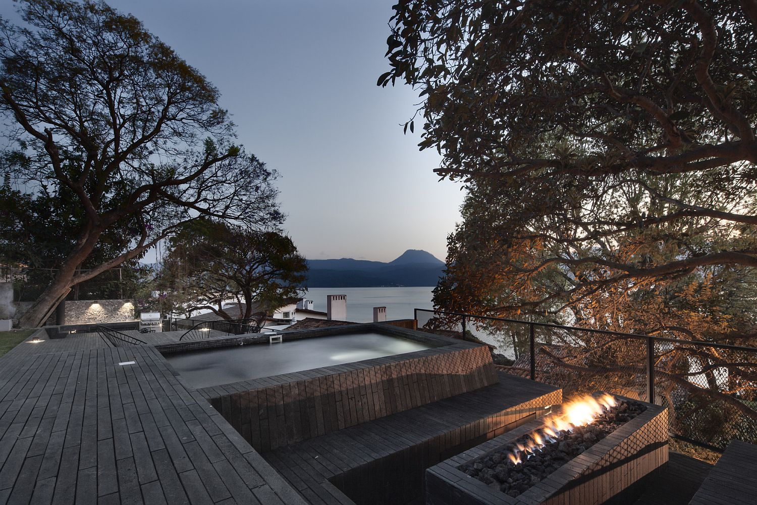 Outdoor sitting area and fireplace along with Jacuzzi that offers Lake views