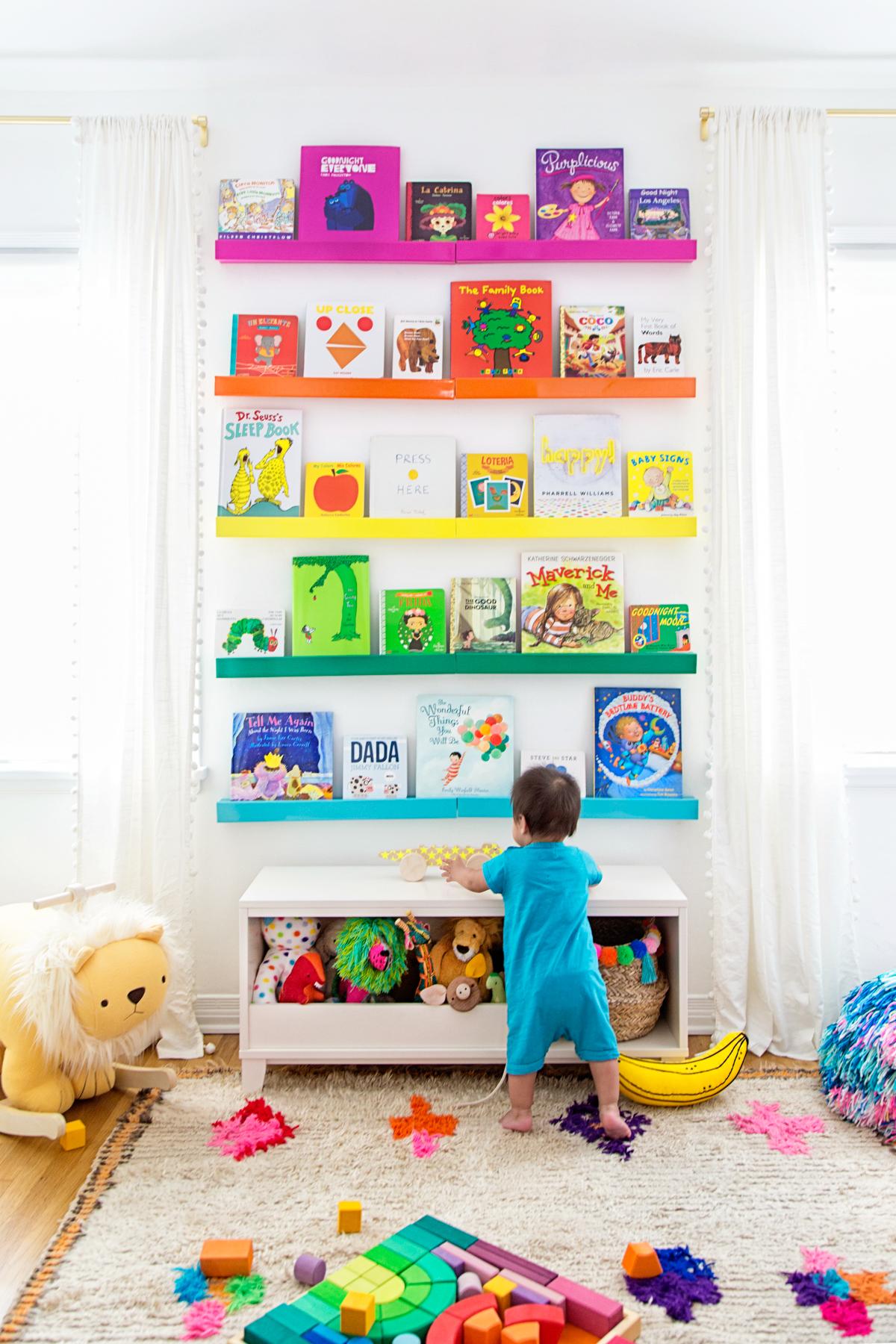 Rainbow bookshelves in a nursery designed by Studio DIY