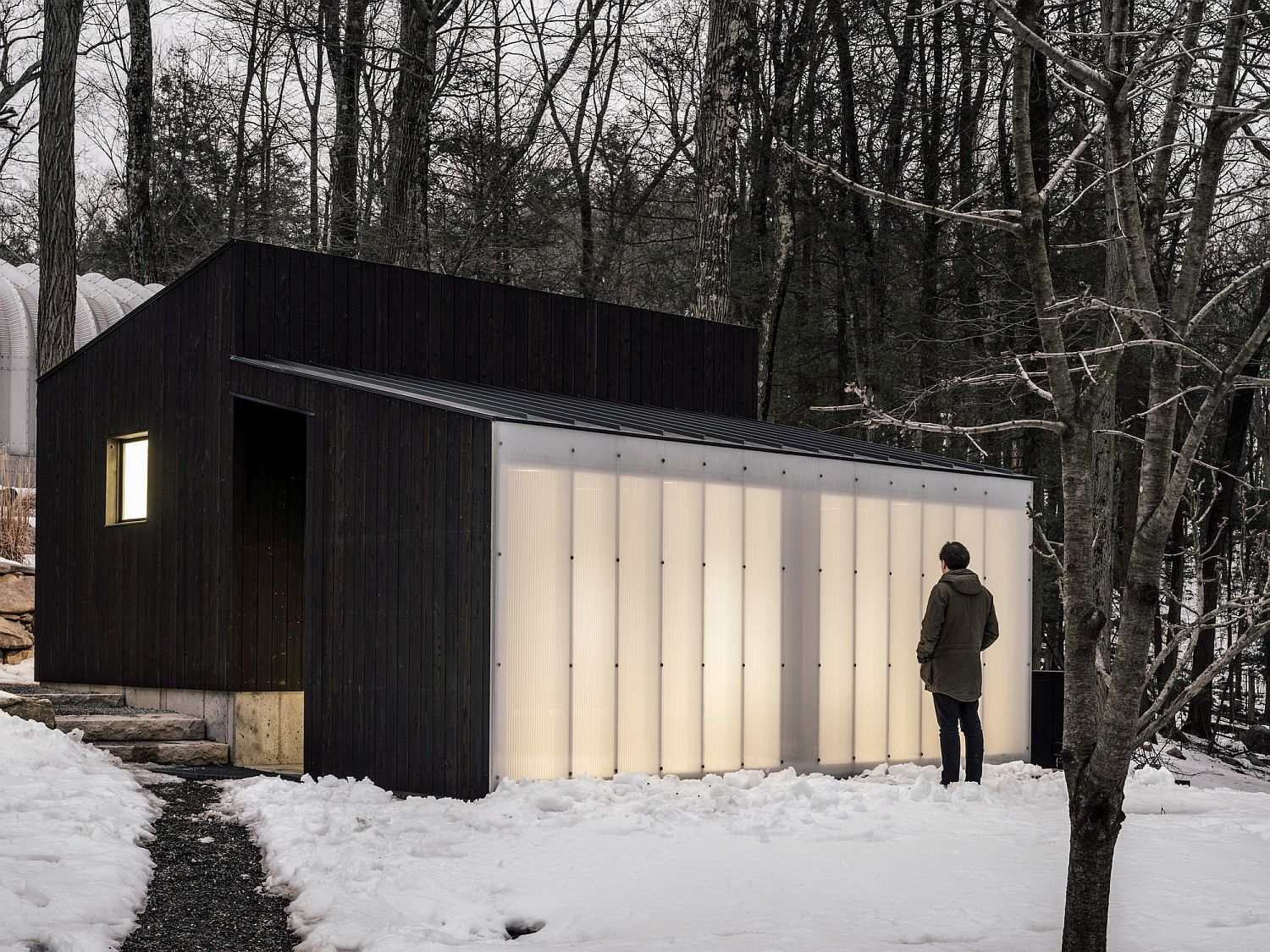 Small-Wooden-Pavilion-with-a-dark-wooden-exterior-and-polycarbonate-wall