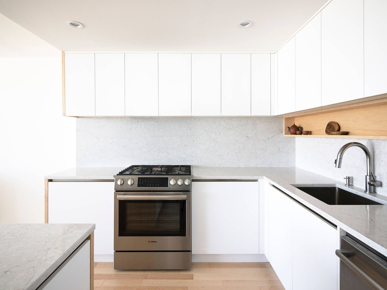 Small white kitchen with open box-style wooden cabinet and lovely lighting