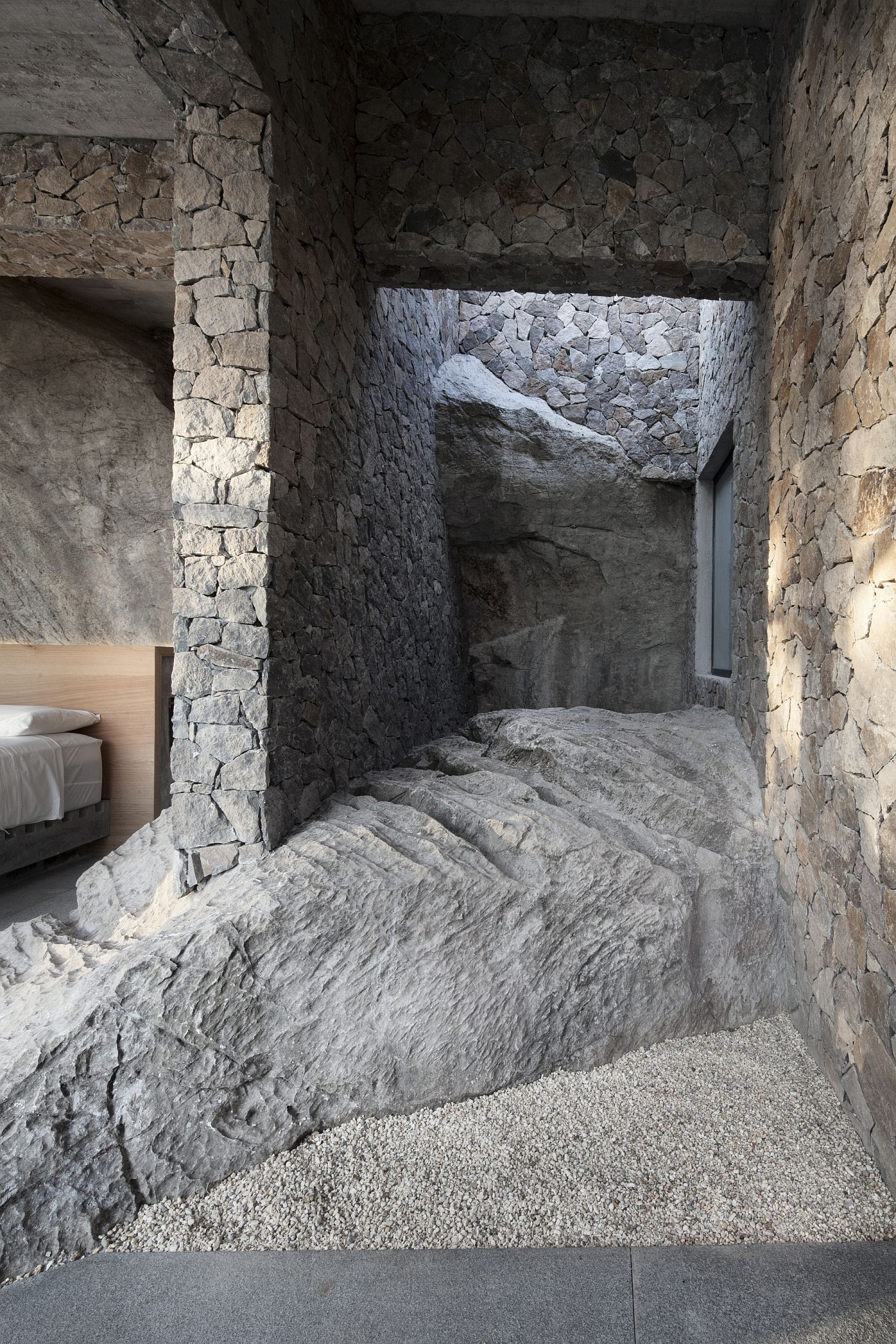 Stone walls coupled with large natural rock give the interior a unique appeal