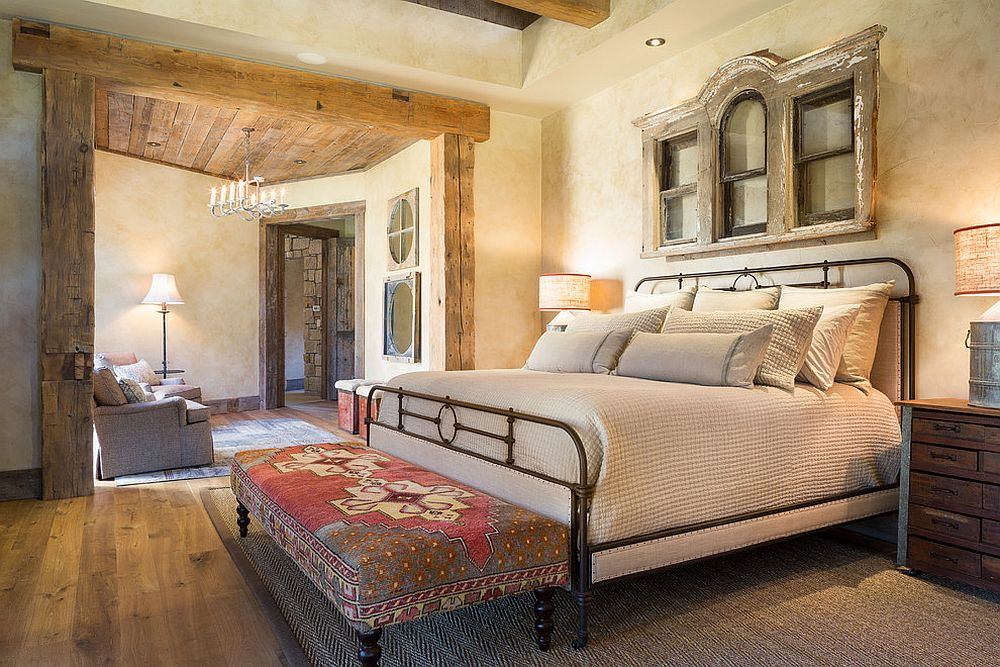 Textured walls and wooden ceiling beams create a cozy, gorgeous bedroom