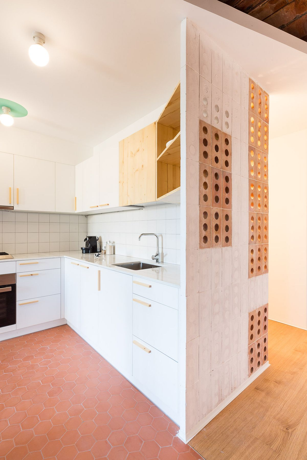 White and wood kitchen of the apartment with hexagonal floor tiles