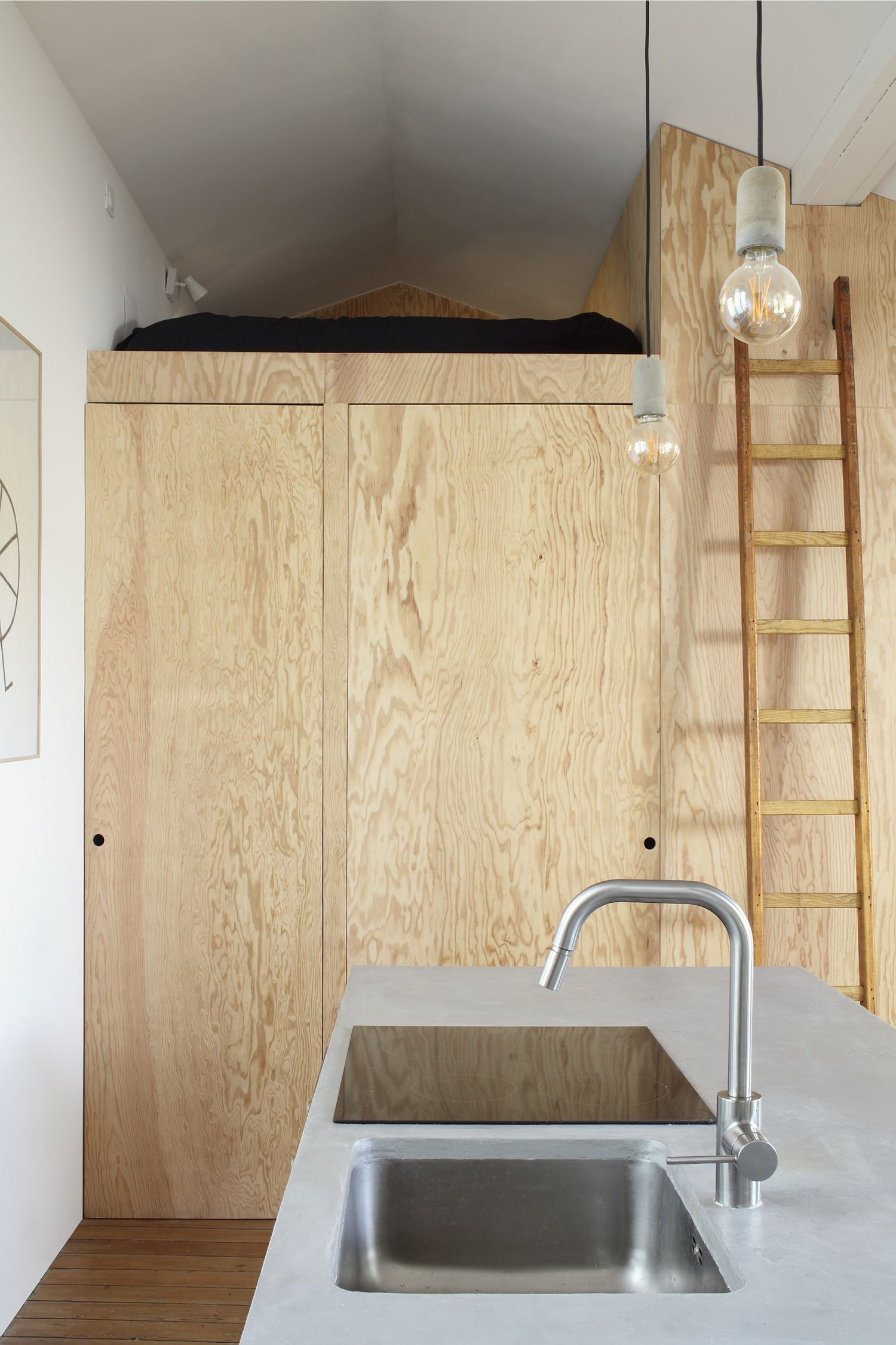 Custom wooden shelves and cabinets shape the interior of this tiny French apartmen