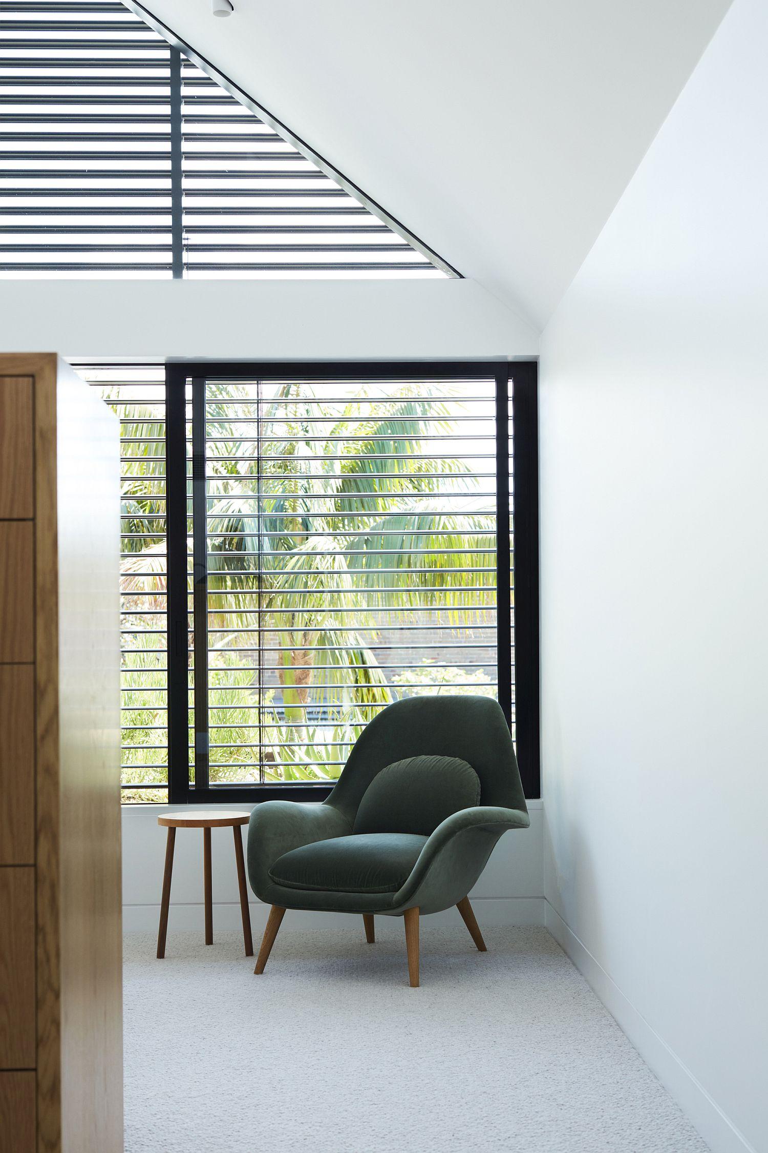 Dark window frames and slats anchor the white room beautifully