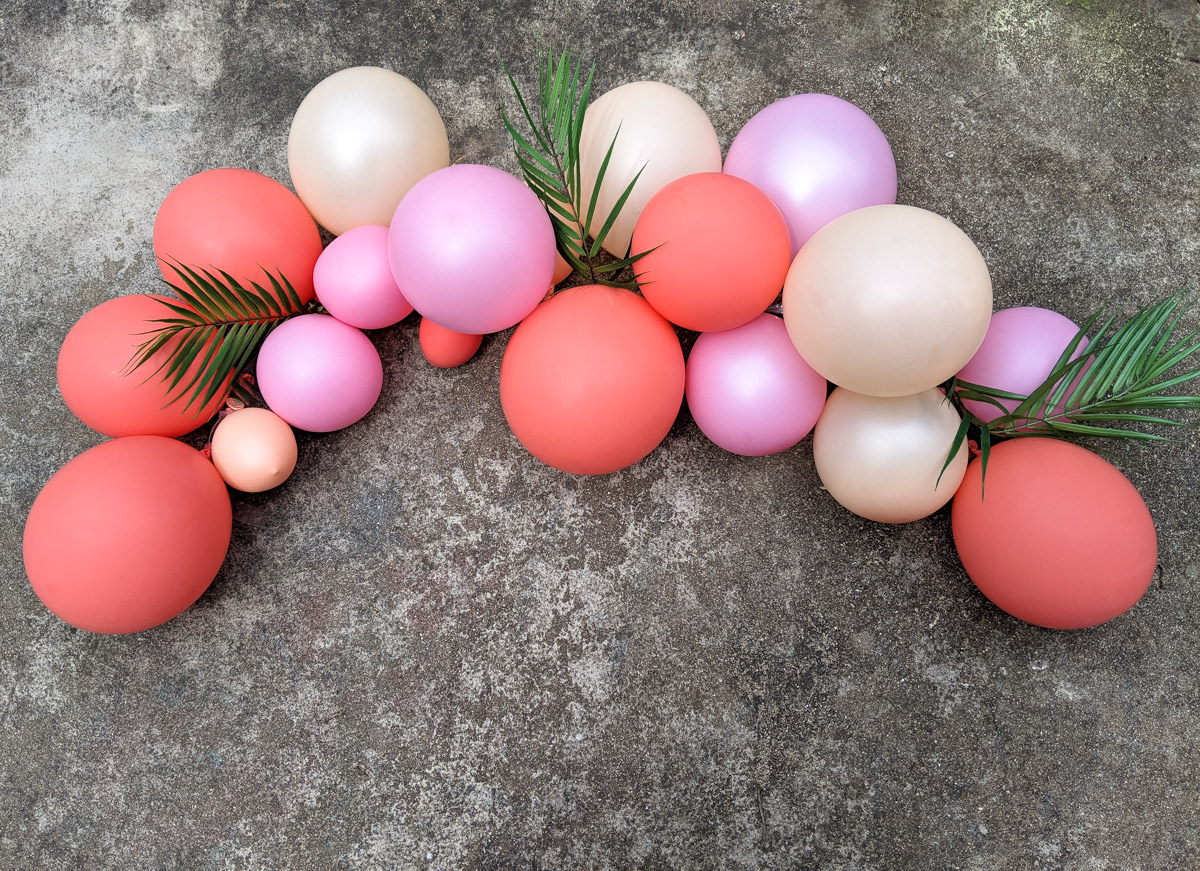 Pink-toned balloon arch with tropical greenery