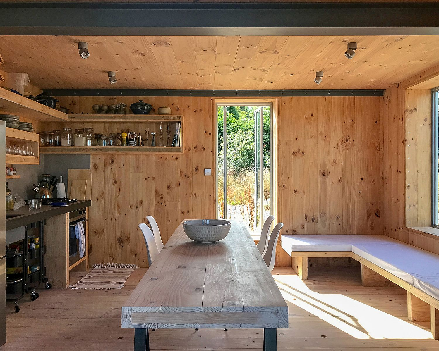 Small kitchen and tiny dining area of the cabin that opens up to the outdoors