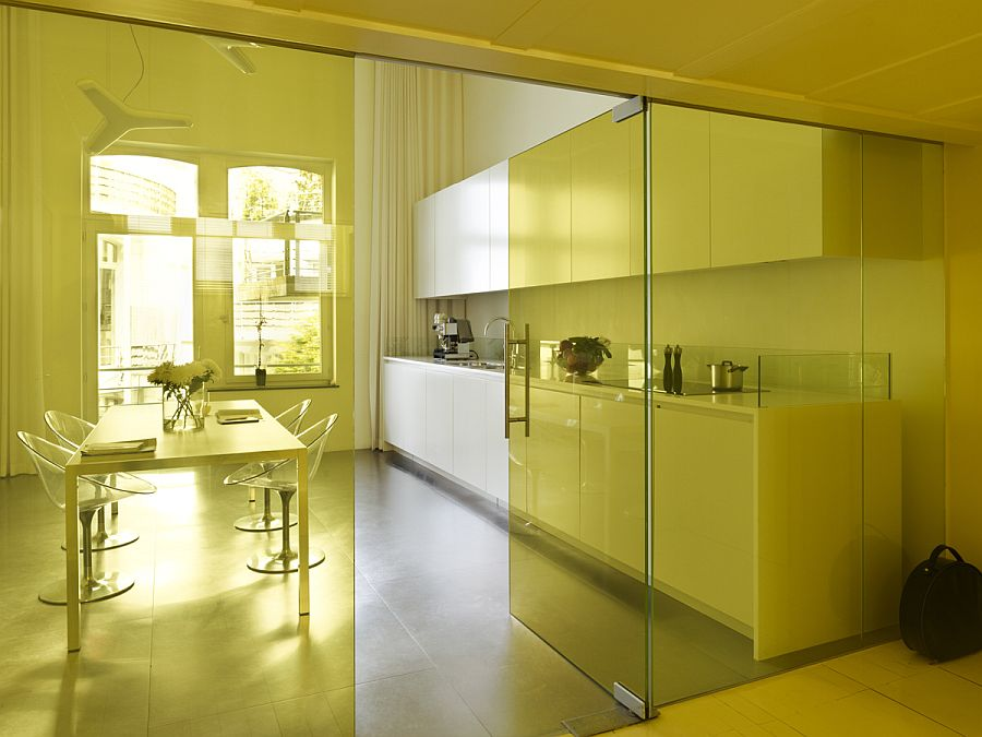 Tinted glass walls in yellow show this Brussels apartment in a whole new light